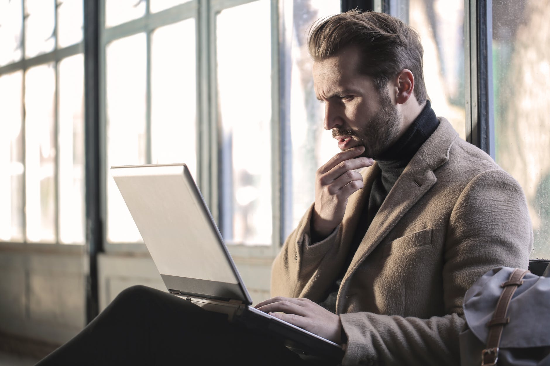man wearing brown jacket and using grey laptop